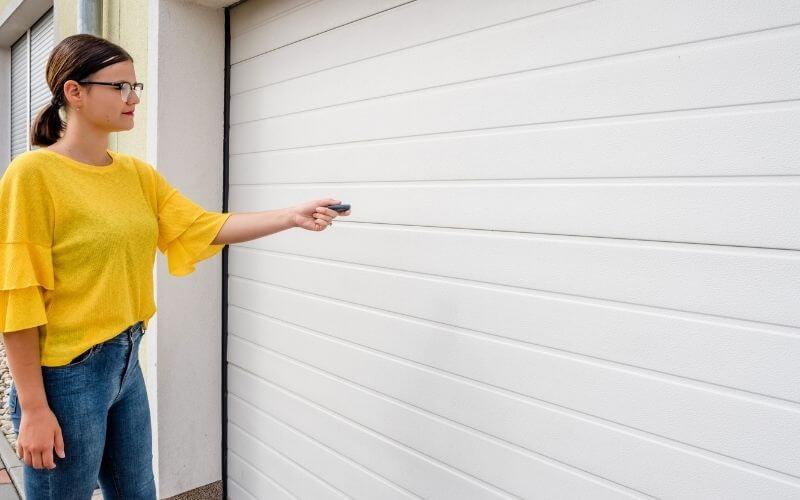 Kobieta otwiera bramę garażową.
